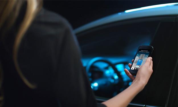 Mujer sosteniendo un smartphone cerca de un coche